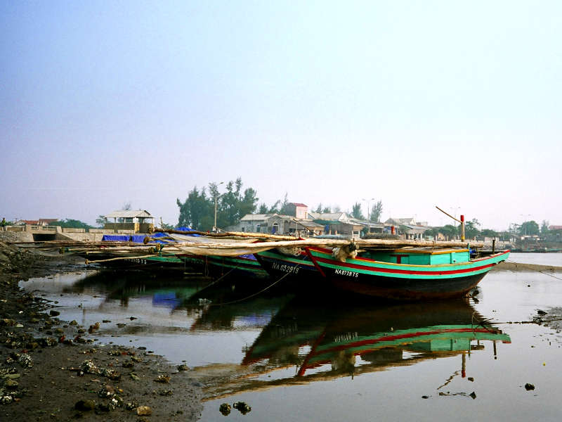 Cua Lo traditional boats on low tide mud flats with Push Ahead nets stowed on board